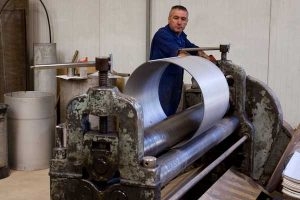 man making sheet metal pipes